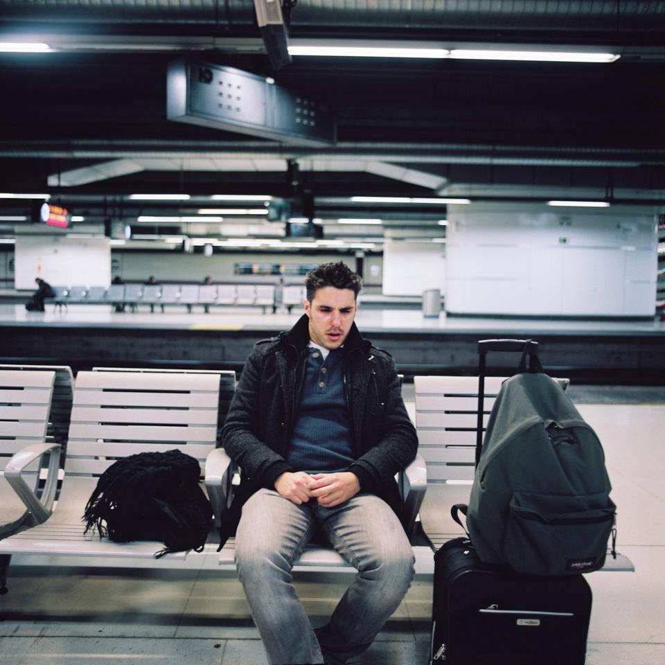 Ein Mann sitzt an einem Bahnsteig.
