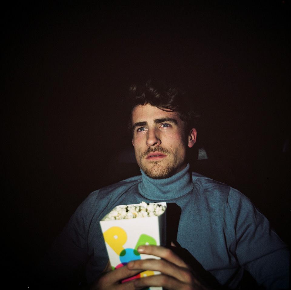 Ein Mann sitzt mit Popcorn im Kino.