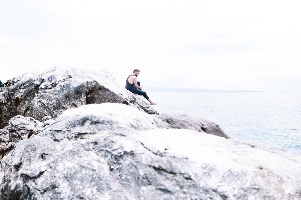 Ein Mann sitzt nachdenklich auf einem Felsen und blickt ins Meer.