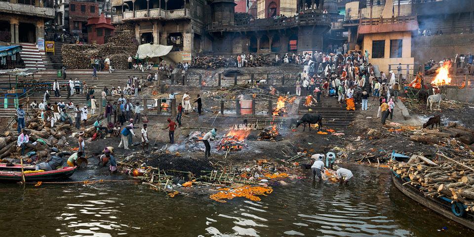 Eine Menschenmenge verarbeitet Holz am Wasser, andere stehen am Rand.
