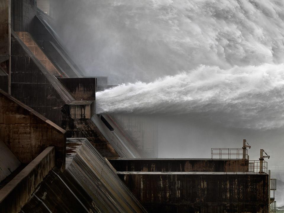 Ein Damm spuckt eine breite Fläche Wasser nach rechts aus.