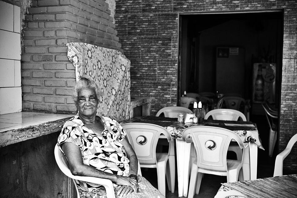 Eine Frau sitzt auf einem Plastikstuhl in einem Imbiss.