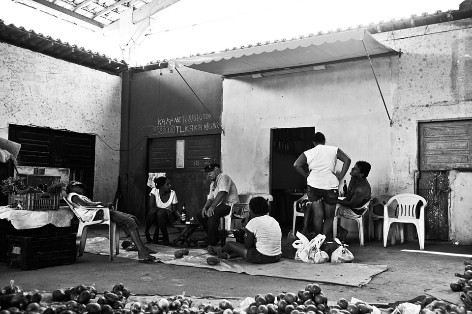 Eine Gruppe Menschen in einem Hof sitzen und stehen beieinander.