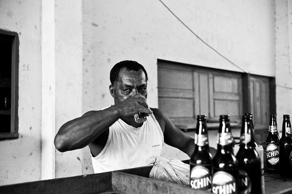 Ein Mann trinkt aus einem Glas. Vor ihm stehen Bierflaschen.