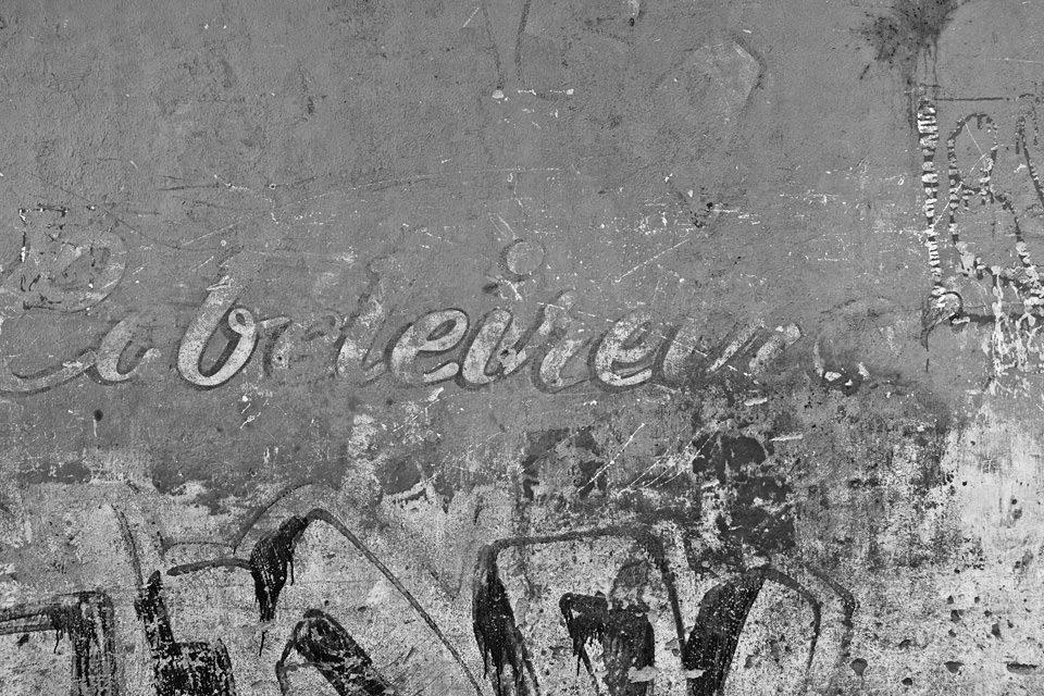 Eine alte Hauswand mit verblichenem Schriftzug.