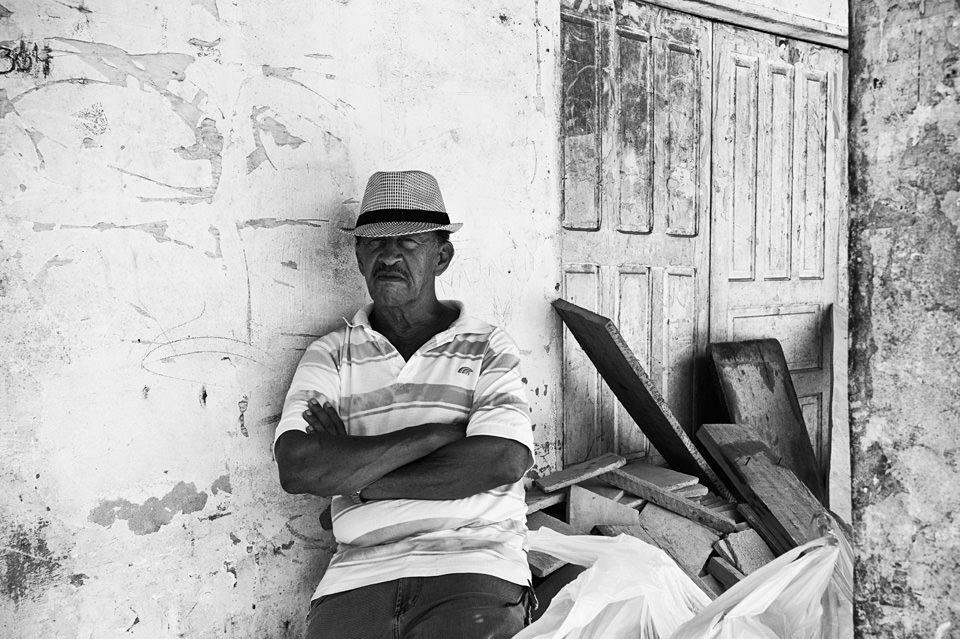 Ein Mann sitzt mit verschränkten Armen auf einer Mauer.