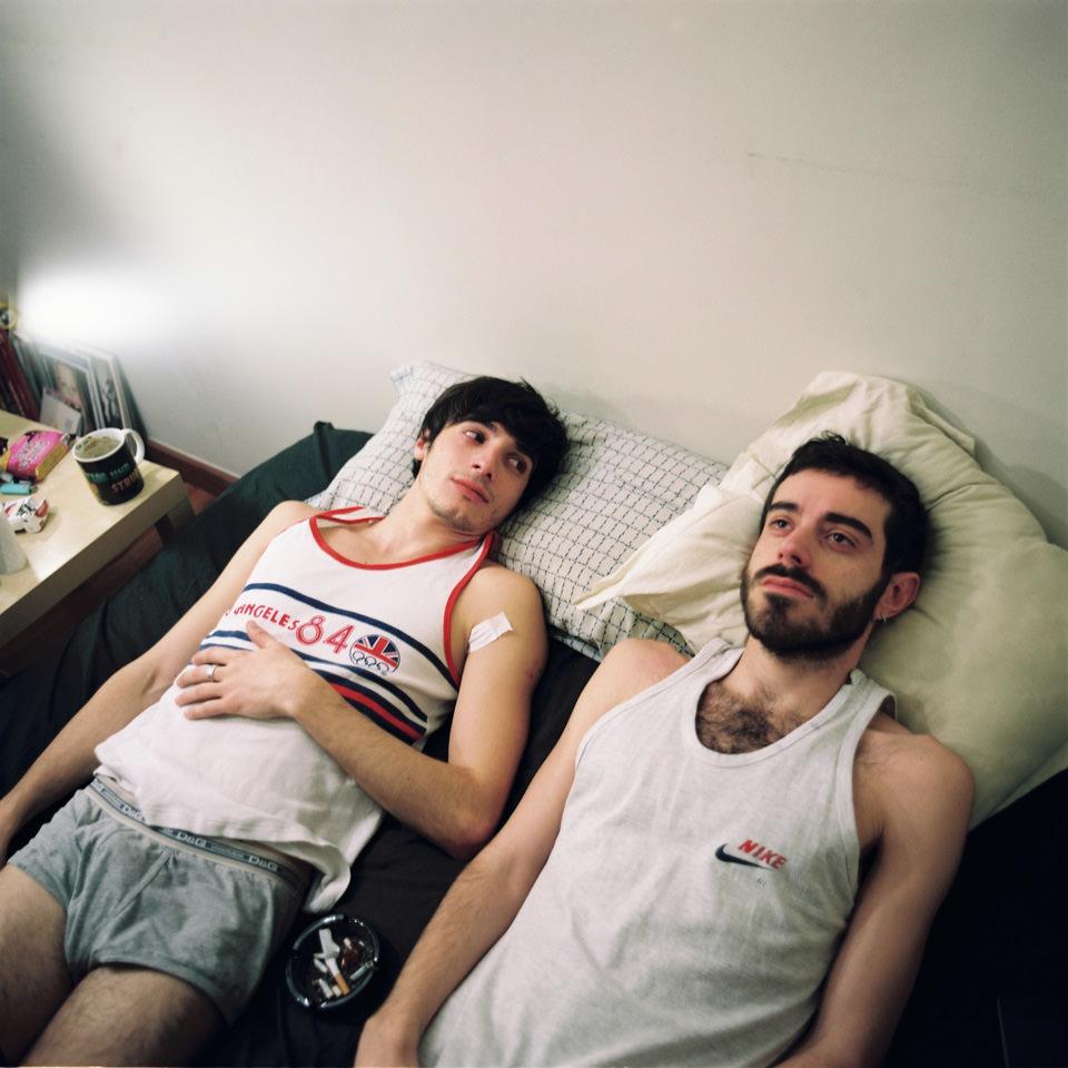 Zwei Männer liegen auf einem Bett.
