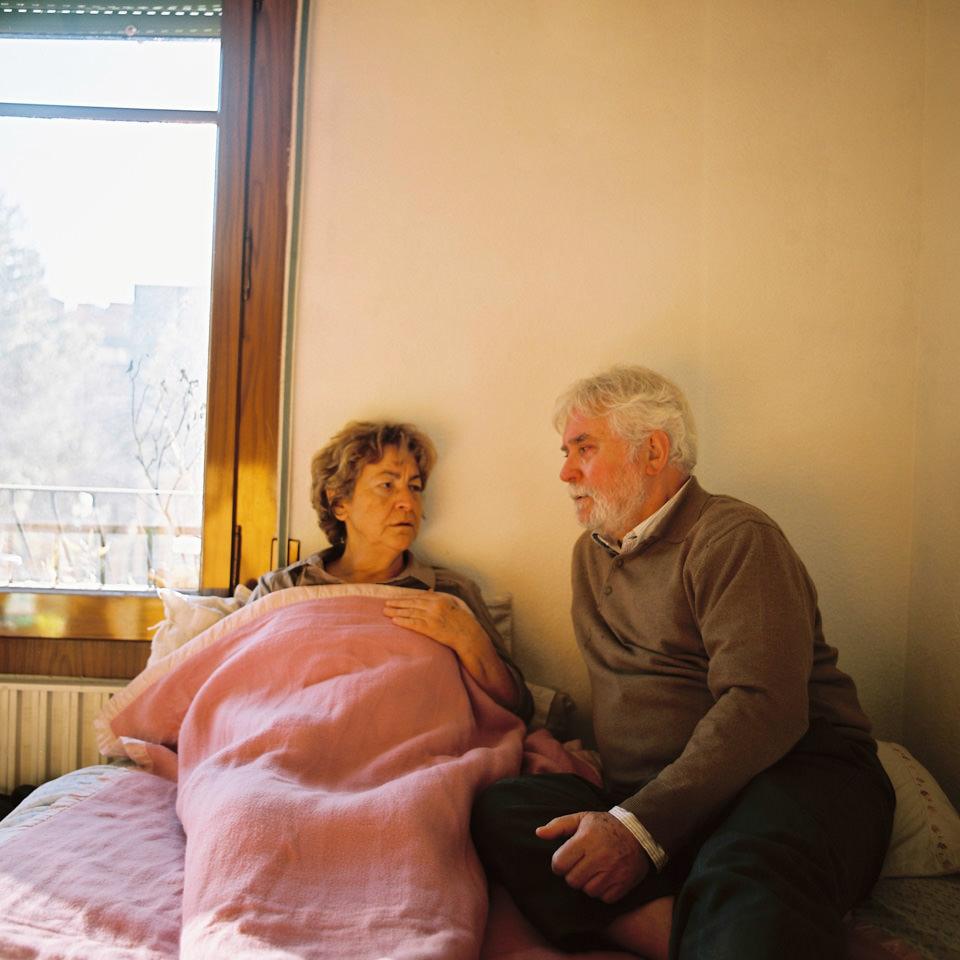 Ein älteres Paar sitzt neben einem Fenster.