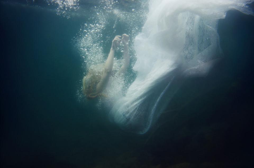 Unterwasserfoto einer fallenden Frau in weißem Kleid