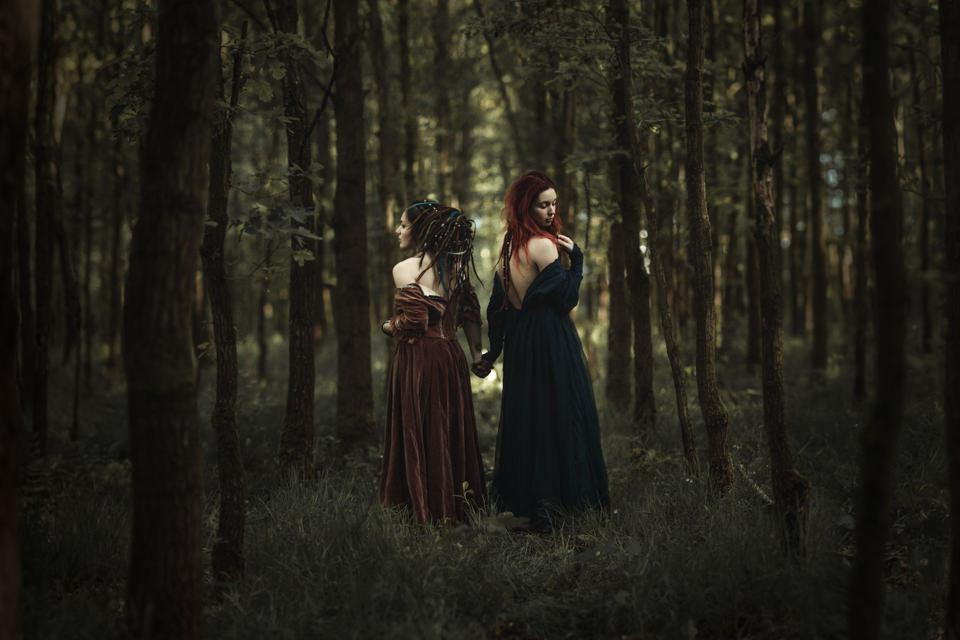 Zwei Frauen stehen Hand in Hand im Wald und sehen in unterschiedliche Richtungen.