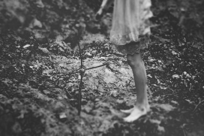 Ein Mädchen steht im Wald vor einem selbstgebastelten Kreuz.