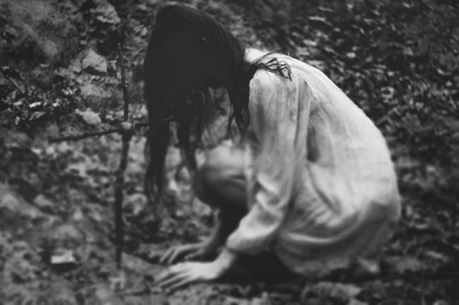 Ein Mädchen hockt auf dem Waldboden vor einem Kreuz.