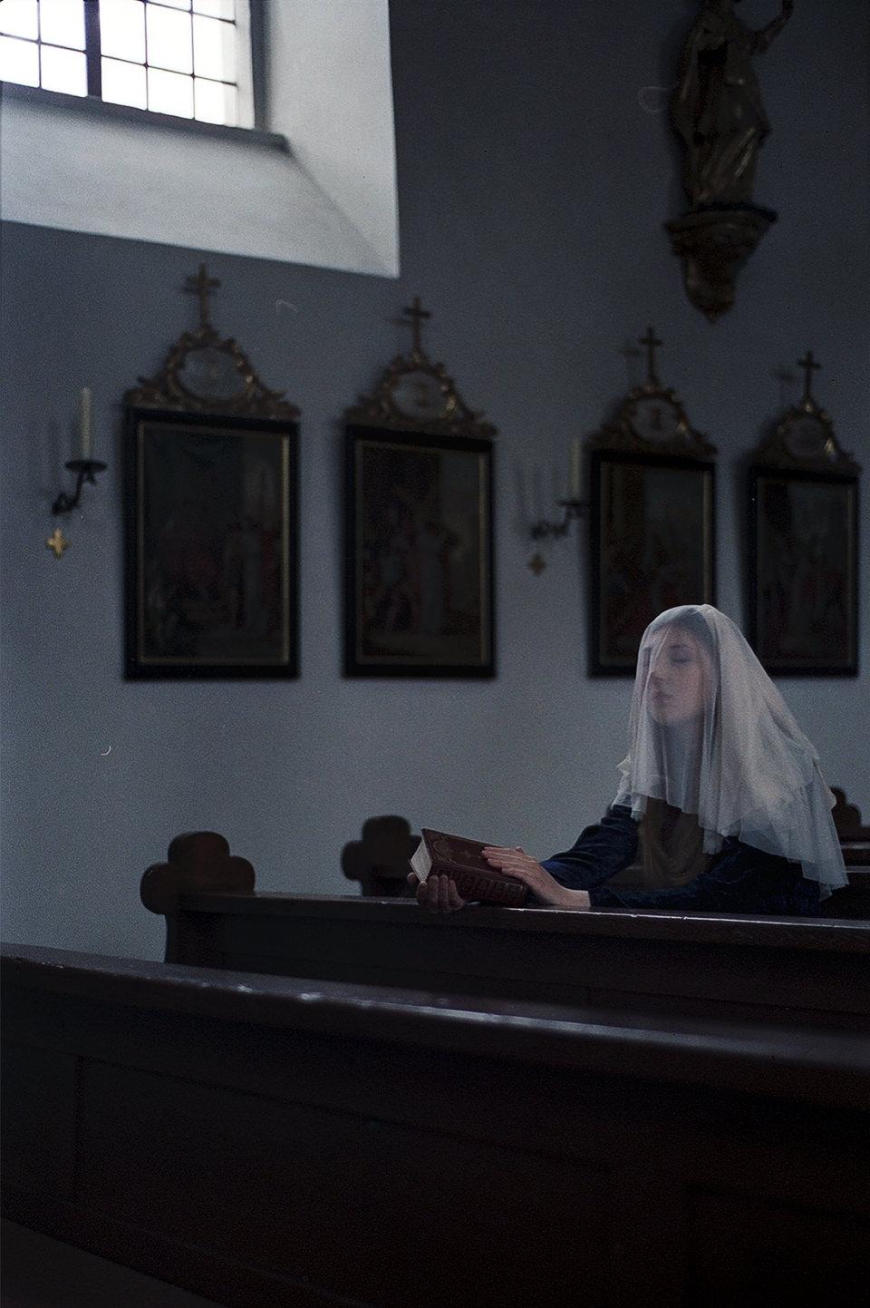 Eine Frau sitzt betend in der Kirche.