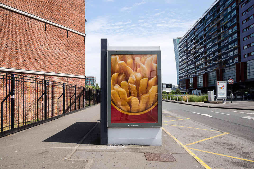 Blick auf eine leere Straße, die von einem großen Plakat mit Pommes Frites geschmückt ist.