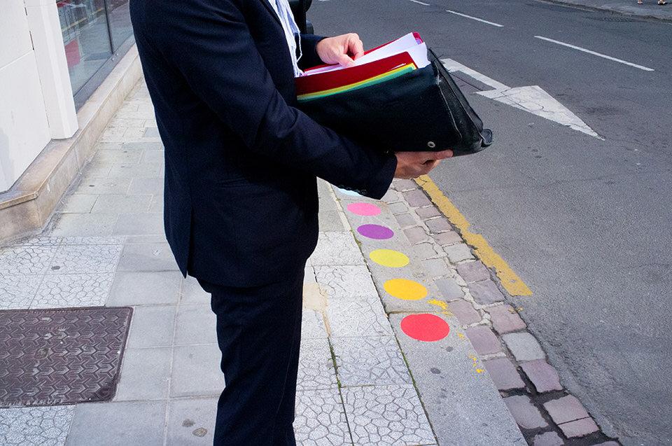 Ein Mann schaut in seine bunten Akten, am Boden mehrere bunte Kreise.
