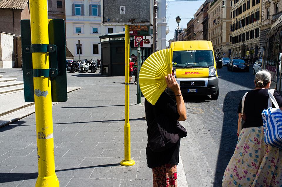 Eine Frau mit gelbem Fächer steht an der Straße und hält sich den Fächer vor das Gesicht.