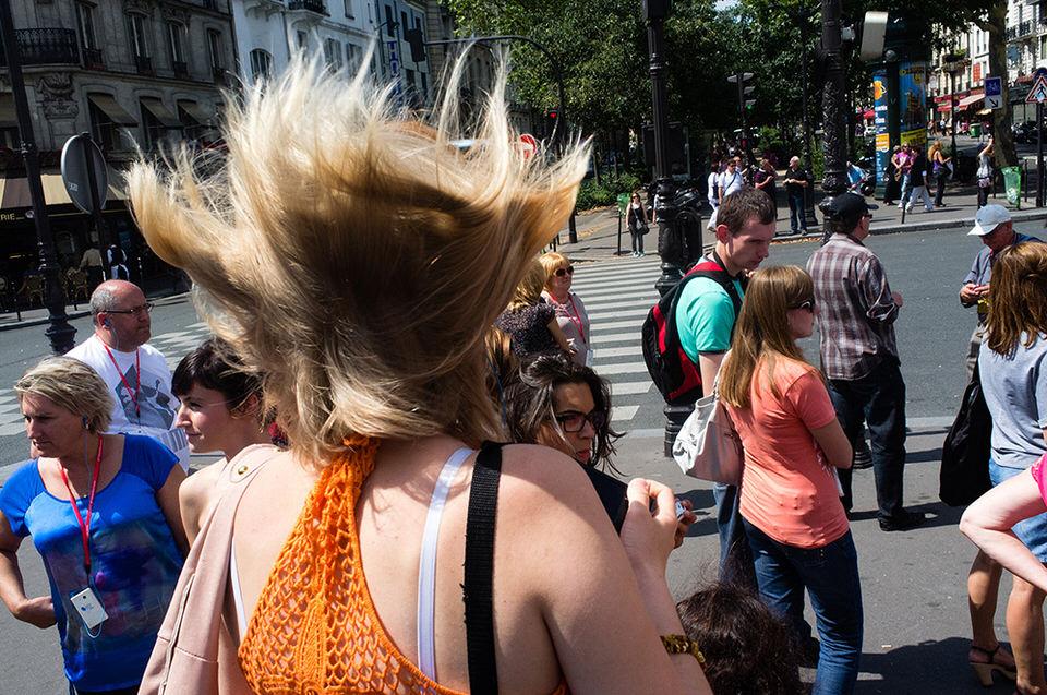 Die Haare einer Frau werden vom Wind nach oben geblasen.