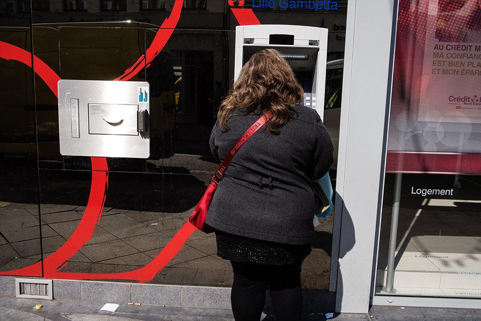 Eine Frau mit roter Tasche steht an einem Geldautomat.