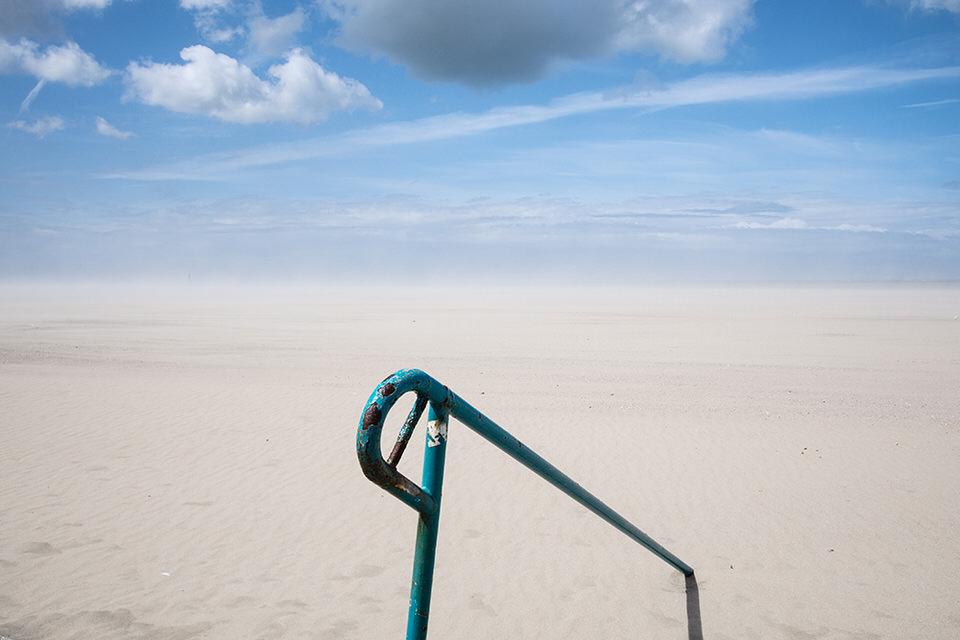 Blick aufs Meer, im Vordergrund ein Geländer.