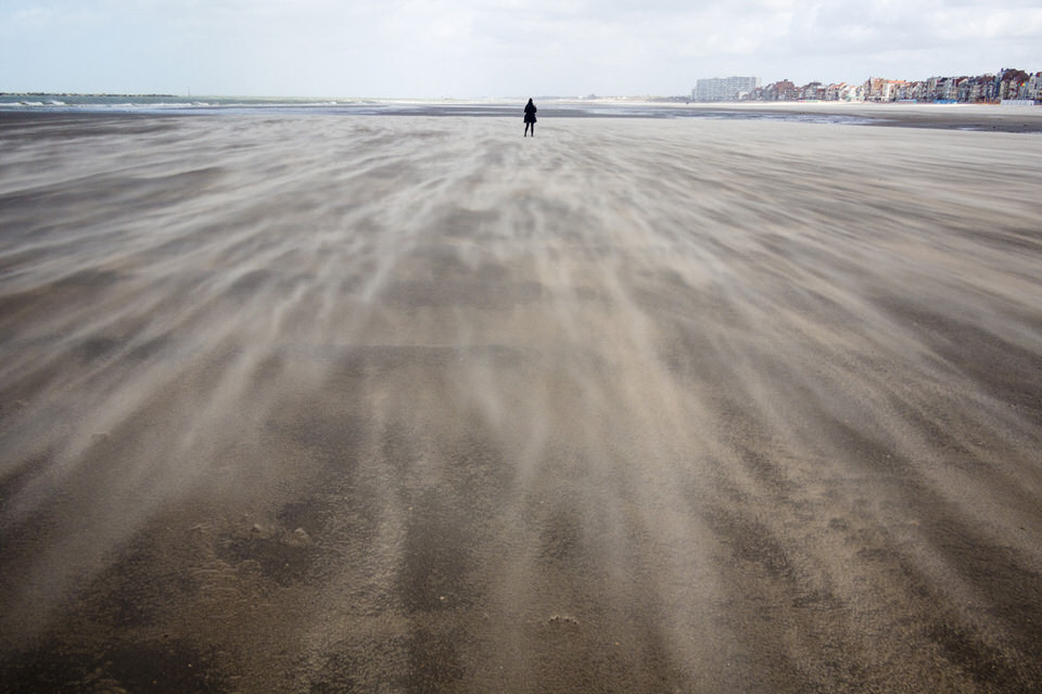 Blick auf eine in der Ferne stehende Person am Meer.