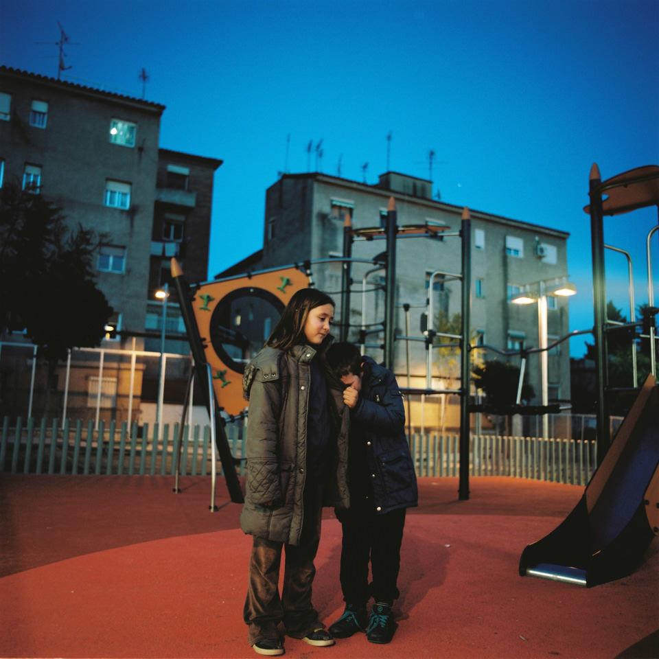 Ein Mädchen und ein Junge stehen auf einem Spielplatz.