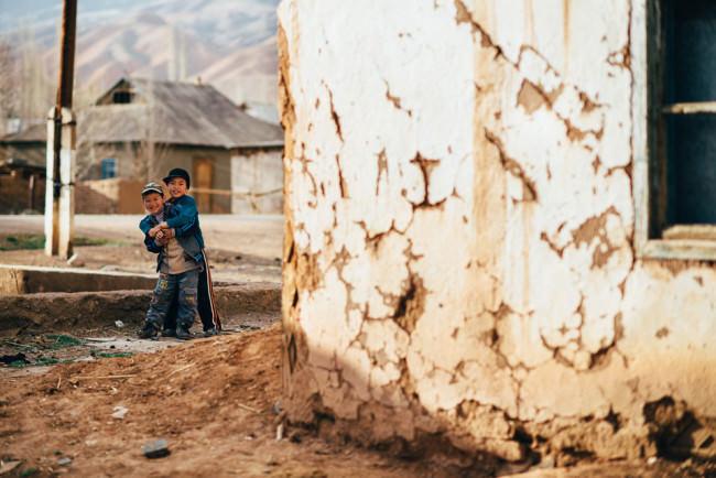 Zwei kirgisische Jungs spielen hinter einer Hütte.