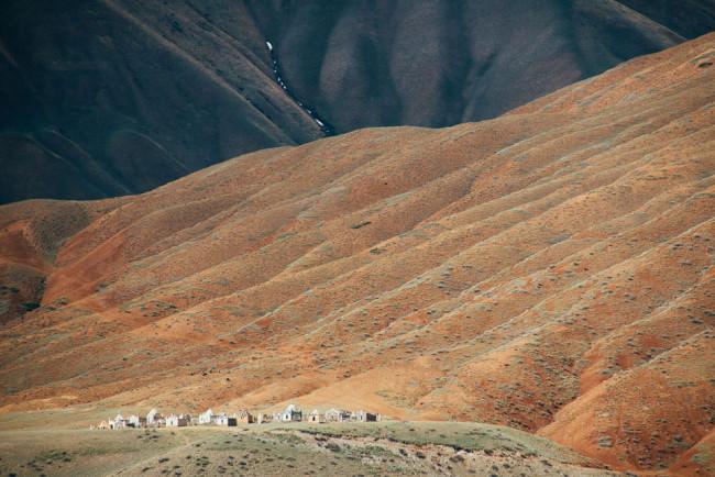 Steingräber erscheinen winzig vor einem gewaltigen Berg.