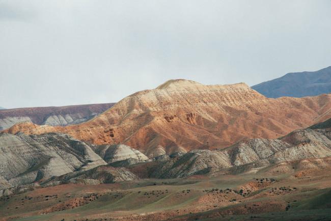 Gesteinsschichten zeichnen sich an einem Bergmassiv ab.