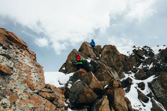 Zwei Bergsteiger erklimmen einen Gipfel.