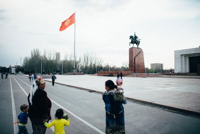 Frauen mit kleinen Kindern stehen vor einem Reiterstandbild.