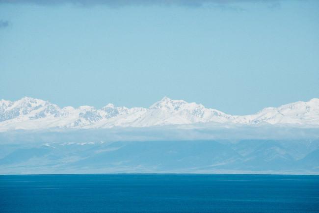 Vor der Kulisse einer schneebedeckten Bergkette liegt ein tiefblauer Gebirgssee.
