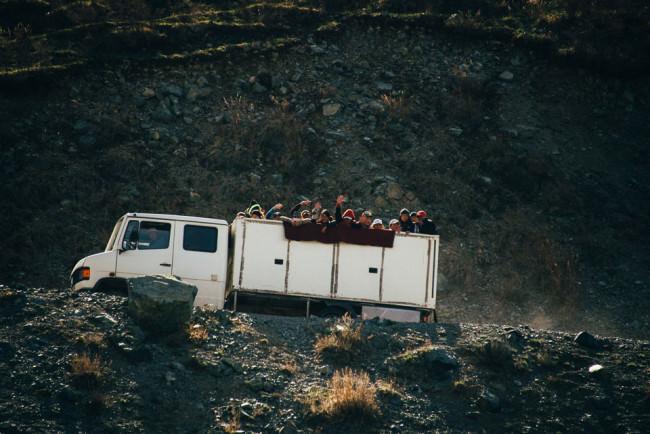 Ein LKW fährt eine steile Bergstraße hinauf. Die Ladefläche ist voll mit winkenden Kindern.