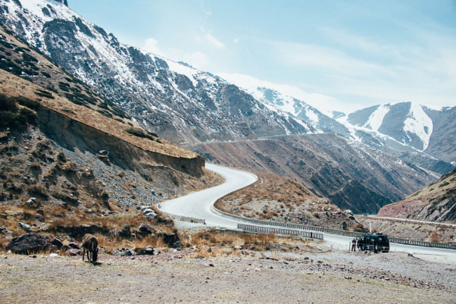 Eine Straße führt durch die kirgisische Berglandschaft. Im Vordergrund weidet ein Esel.