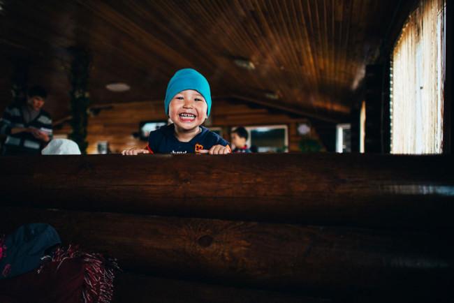 Ein kleiner Junge schuat mit breitem Grinsen über eine Holzbrüstung.