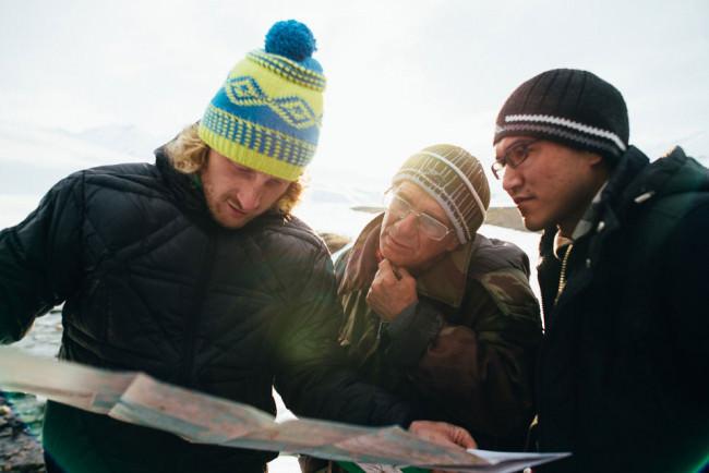 Drei Männer schauen auf eine Karte.