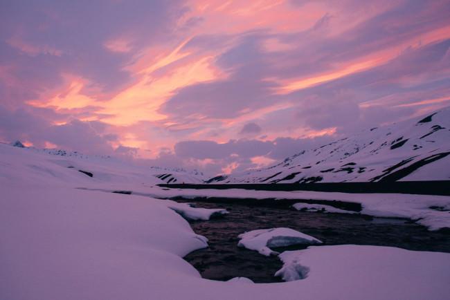 Abendhimmel über einem durch eine schneebedeckte Berglandschaft fließenden Fluss.