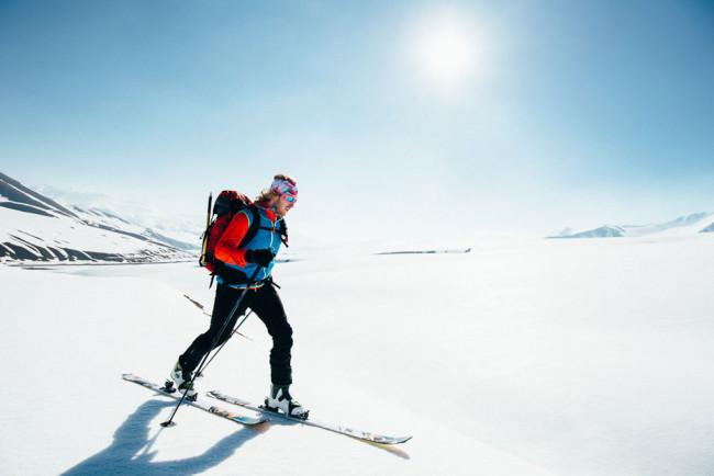 Bei strahlendem Sonnenschein ist ein Mann auf Skiern durch den Schnee unterwegs.