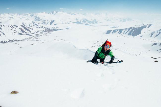 Ein Mann kraxelt einen schneebedeckten Hang hinauf.