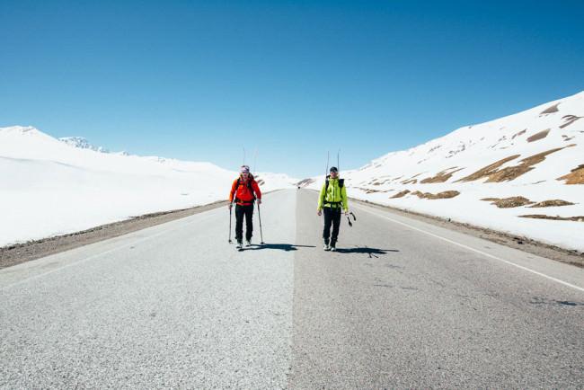 Zwei Männer in Bergsteigerkluft laufen durch eine Schneelandschaft eine asphaltierte Straße entlang.