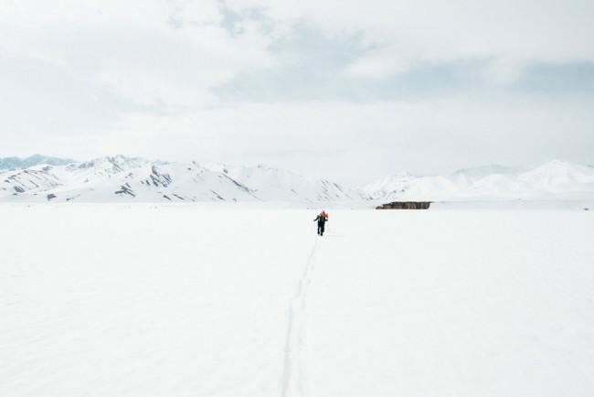 Ein Skiläufer bewegt sich über eine weite weiße Ebene.