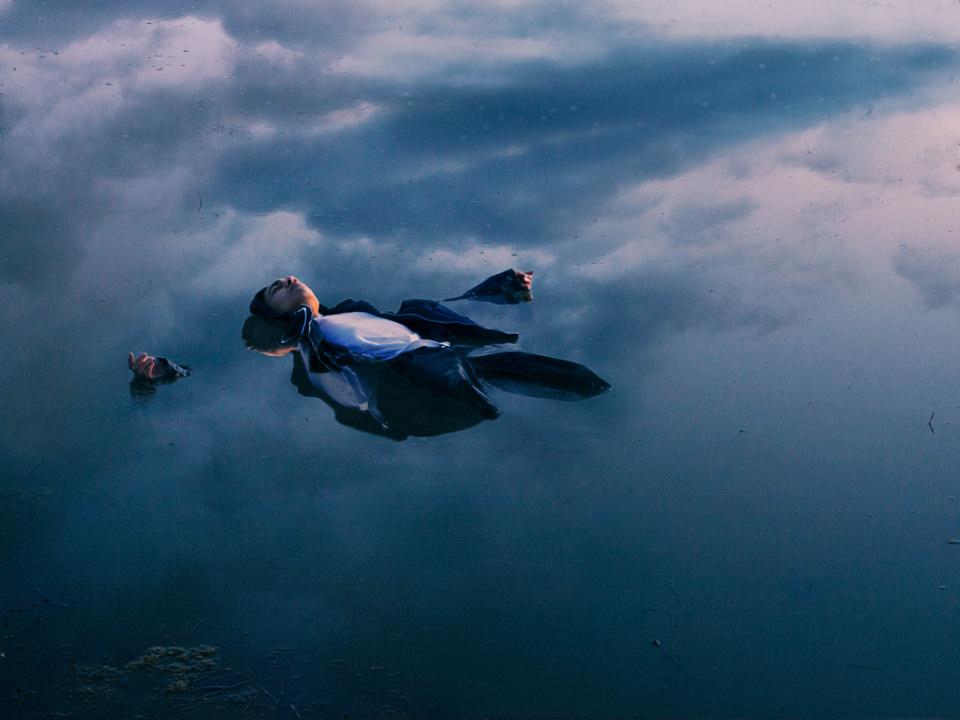 Ein Mann liegt mit dem Rücken nach unten und ausgebreiteten Armen im Wasser, auf dem sich Wolken spiegeln.