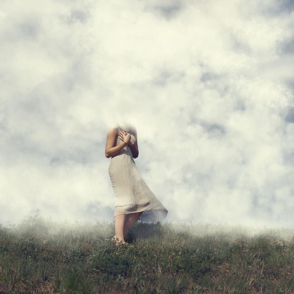 Eine Frau steht mit vor der Brust gekeuzten Armen auf einer Wiese. Wolken liegen tief auf der Wiese und verdecken ihr Gesicht.