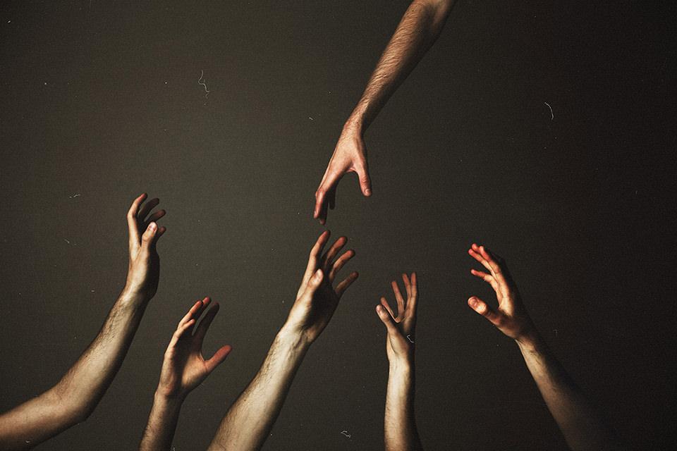 Vier Arme von unten strecken sich nach oben zu einer weiteren Hand.