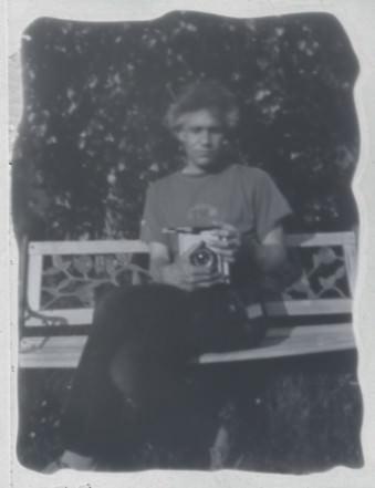 Ein Mann mit einer Kamera sitzt auf einer Bank.