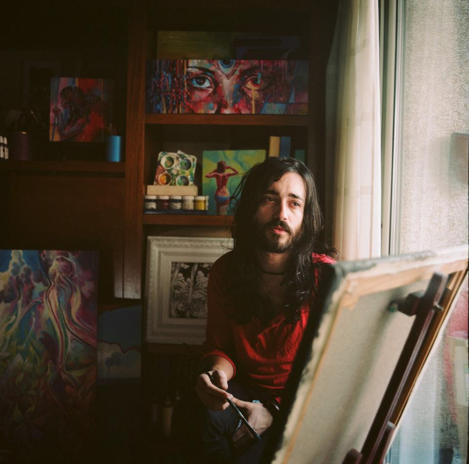 Ein Maler sitzt in einem Atelier.