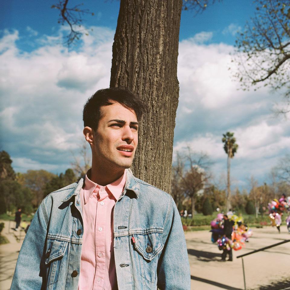Ein Mann steht vor einem Baum.
