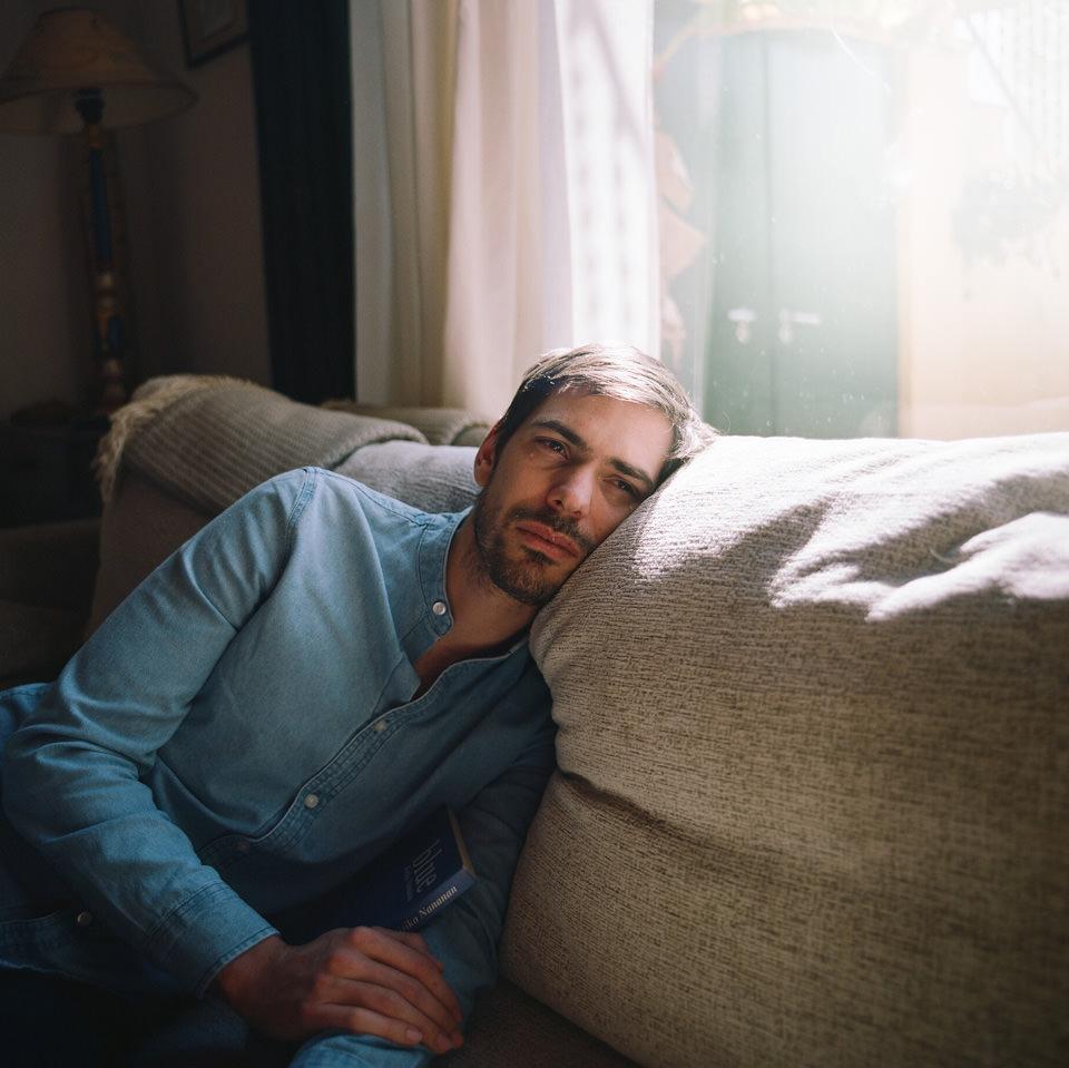 Ein Mann liegt weinend auf einem Sofa.