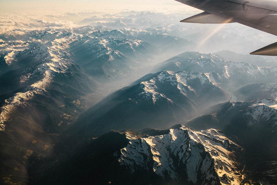 Blick aus dem Flugzeug auf die Alplen, die vom Licht durchflutet werden.