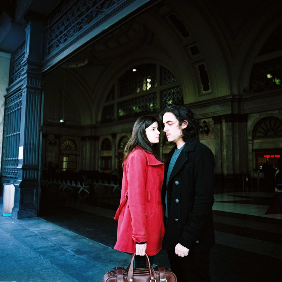 Ein Paar steht vor einer Bahnhofshalle.