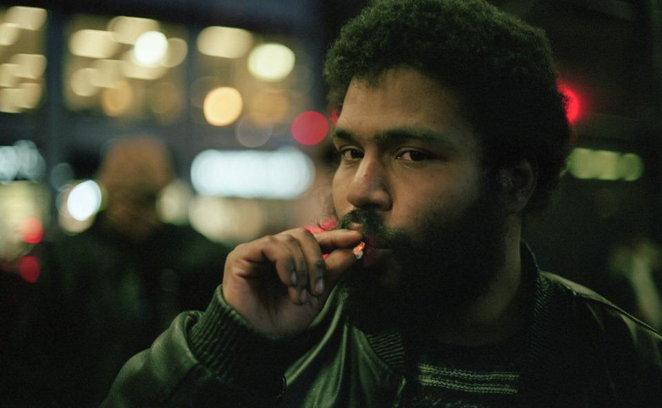 Straßenfotografie: Portrait eines Mannes, der an einer Zigarette zieht.